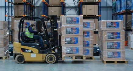 man lifting boxes in warehouse with forklift